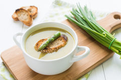 Bol de soupe à asperge avec la lance et le pain d'asperge sur la coupe Photos stock
