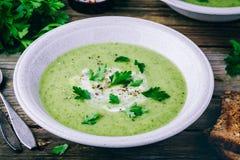 Bol de soupe verte à crème de courgette avec le persil frais Images libres de droits