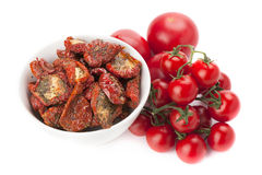 Bol de tomates séchées au soleil et tas des tomates fraîches mûres Image stock