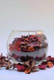Bol de vidrio con derramamiento rojo del popurrí Foto de archivo libre de regalías