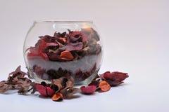 Bol de vidrio con derramamiento rojo del popurrí Imagen de archivo libre de regalías