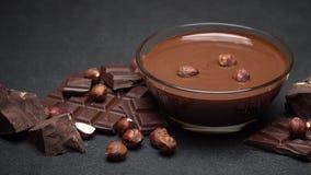 Bol de vidrio de crema del chocolate o chocolate derretido, pedazos de chocolate y avellanas metrajes
