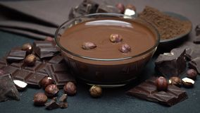 Bol de vidrio de crema del chocolate o chocolate derretido, pedazos de chocolate y avellanas almacen de metraje de vídeo