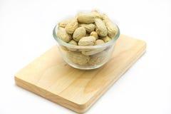 Bol de vidrio de cacahuetes en el tablero de madera, fondo blanco Foto de archivo
