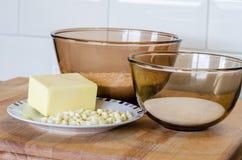 Bol de vidrio de cocer el azúcar y la mantequilla de la harina de Ingedients en un Pla imagen de archivo
