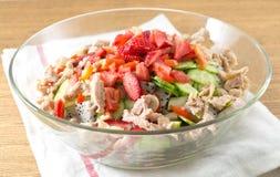 Bol de vidrio de ensalada de pollo deliciosa con las frutas Foto de archivo