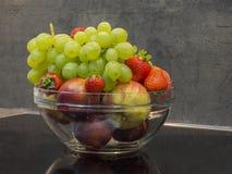 Bol de vidrio de fruta lavada fresca - manojo de las manzanas del strawb de las uvas Foto de archivo