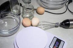 Bol de vidrio, escalas electrónicas y un batidor de una licuadora en un fondo blanco Primer en escalas fotografía de archivo libre de regalías