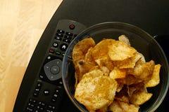 Bol de vidrio llenado de patatas fritas del eneldo y de la cebolleta y de un telecontrol de la TV en un soporte negro de la TV imágenes de archivo libres de regalías