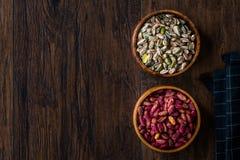 Bol en bois cru et rôti de pistaches épluchées sans Shell/sans Shell photographie stock libre de droits
