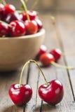 Bol en bois de cerises sur la table Photo stock