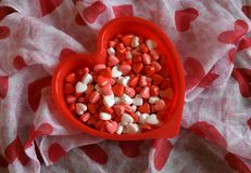 Bol en forme de coeur de sucrerie sur un fond floral coloré Photo libre de droits