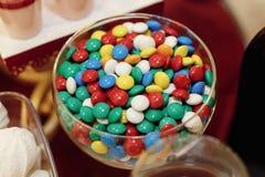 Bol en verre élégant avec les sucreries colorées sur la table, esprit de friandise photographie stock libre de droits