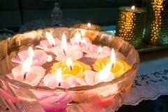 Bol en verre avec les bougies de flottement et les bougies d'or dans le backgro Photo stock