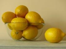 Bol en verre de citrons jaunes mûrs juteux sur une étagère en bois grise Riches organiques en bonne santé de fruit tropical de vi photos libres de droits