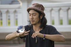 Bol en verre de jonglerie d'interprète de rue devant des passants sur la route de Khao San de rue Bangkok, Thaïlande Photographie stock