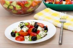 Bol en verre et plat transparents avec de la salade grecque, fourchette Image libre de droits