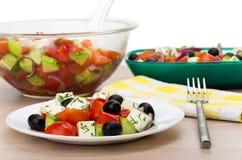 Bol en verre et plat transparents avec de la salade grecque, fourchette, serviette Images libres de droits