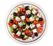 Bol en verre transparent avec de la salade grecque d'isolement sur le blanc Image stock
