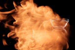 Bol en verre vide dans les flammes du feu Images libres de droits