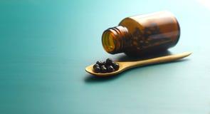 Bol noir sur la cuillère et la bouteille en bois sur le fond vert image stock