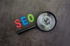 Bol op meer magnifier glas, alfabetwoord SEO in rood, blauw en gre stock afbeelding