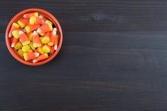 Bol orange de bonbons au maïs sur le fond foncé Image stock