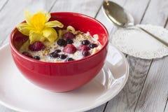 Bol rouge de céréale avec des fraises avec des baies photo libre de droits