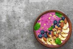 Bol sain de smoothie d'acai de petit déjeuner avec la banane, la myrtille, la granola, les amandes, le potiron et les graines de  photos libres de droits