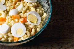 Bol servant de salade de macaronis complété avec des oeufs et des poivrons oranges photo libre de droits