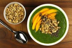 Bol vert de smoothie avec les mangues, la granola et les graines de chia Photographie stock
