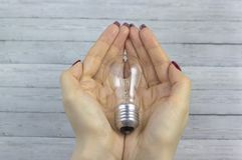 Bol in vrouwenhand, Realistisch fotobeeld Zet wolfram gloeilamp met hand aan royalty-vrije stock afbeeldingen