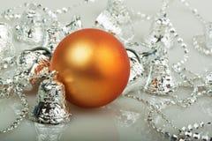 Bola alaranjada do Natal com sinos de prata Imagem de Stock Royalty Free