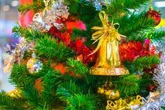 Bola amarela que pendura no ramo da árvore de Natal no backg Fotos de Stock