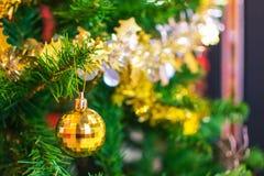 Bola amarela que pendura no ramo da árvore de Natal no backg Fotografia de Stock Royalty Free