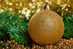 Bola amarilla de la Navidad con la rama verde del abeto Imágenes de archivo libres de regalías
