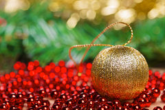 Bola amarilla de la Navidad en gotas rojas Foto de archivo