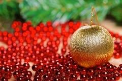 Bola amarilla de la Navidad en gotas rojas Fotografía de archivo libre de regalías