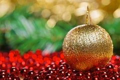 Bola amarilla de la Navidad en gotas rojas Fotografía de archivo