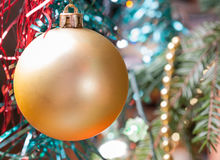 Bola amarilla de la Navidad en una rama Fondo enmascarado Foto de archivo libre de regalías
