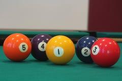 Bola amarilla del billar con el número uno en él con otras bolas coloridas colocadas en fila en una tabla Imágenes de archivo libres de regalías