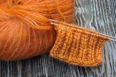 Bola anaranjada de las lanas del moer que hace punto y agujas que hacen punto en el viejo fondo rústico de madera Foto de archivo