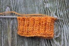 Bola anaranjada de las lanas del moer que hace punto y agujas que hacen punto en el viejo fondo rústico de madera Imagenes de archivo