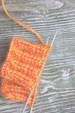 Bola anaranjada de las lanas del moer que hace punto y agujas que hacen punto en el viejo fondo rústico de madera Foto de archivo libre de regalías