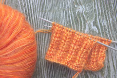 Bola anaranjada de las lanas del moer que hace punto y agujas que hacen punto en el viejo fondo rústico de madera Fotografía de archivo libre de regalías
