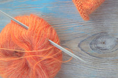 Bola anaranjada de las lanas del moer que hace punto y agujas que hacen punto en el viejo fondo rústico de madera Fotos de archivo libres de regalías