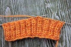 Bola anaranjada de las lanas del moer que hace punto y agujas que hacen punto en el viejo fondo rústico de madera Imagen de archivo