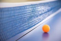 Bola anaranjada para el tenis en una tabla azul con una rejilla Imagenes de archivo