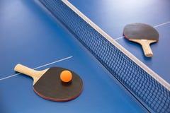 Bola anaranjada para los tenis de mesa y dos estafas de co rojo y negro Fotos de archivo