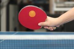 Bola anaranjada sostenida de los tenis de mesa del counterhit del cuarto delantero cerca de la red en el bl Fotografía de archivo libre de regalías